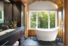 Pretty cool bathroom with river rocks a surrounding tub and a gorgeous view while you relax. Bringing the outdoors in.