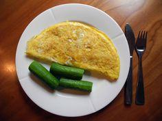 Omelett med skinke, ost og tomat inni, og snacksagurker på siden.