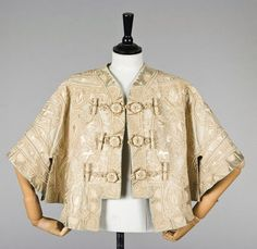 Callot Soeurs short cape, 1901, printed gold on ivory silk label 'Callot Soeurs' 24 Rue Taitbout', the cream wool ground couched and embroidered with oriental inspired raised-work palmettes in ivory silk, tabbed hem, large silk wrapped buttons and toggles, edged and lined in pale brown satin.