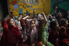 Credits: AP Photo/Nathalie Bardou 20 ottobre 2012. Un gruppo di bambine canta una canzone, diretto da un insegnante, alla periferia di Islamabad, in Pakistan, dove sono sfollate con le loro famiglie, in fuga dalle aree tribali in cui sono in corso scontri con l'esercito.