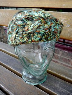 Knitted headband in greens and oranges.