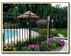 Ornamental aluminum three rail fence around pool - Pool fence landscaping ideas ...