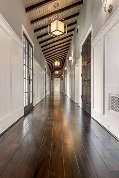 Long hall features a sloped ceiling, dark stained wood beams and caged Lanterns with Paper Shades. Hall also features top part of walls painted gray and lower walls clad in board and batten. Elizabeth Garrett Interiors. #hallwaysandentrys