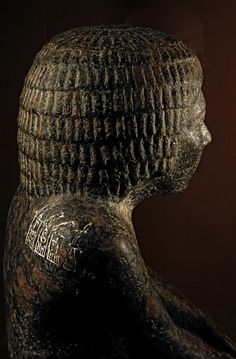 Hetepdief wearing a short wig with small locks and a skirt. His name and titles are inscribed on the base of the statue, while the Horus names of the three first kings of the Second Dynasty are on his right shoulder. These kings are Hetepsekhemwy and Ninetjer Raneb. It seems that Hetepdief served as a priest in their mortuary temples. ~A carved granite statue of the priest, Hetepdief.