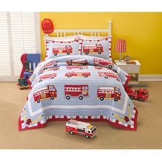 Decorate your child's bedroom with bright and cheery colors using this firetruck applique quilt bedding set. The patchwork quilt features a navy background covered with bright, red firetrucks that provide a fun addition to any kid's bedroom.