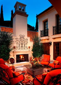 Iron armchairs with vibrant red cushions enclose a cozy sitting area and accent the iron railings on the stucco home exterior. A large outdoor fireplace serves as the focal point in front of a large wicker coffee table, creating an inviting conversation area.