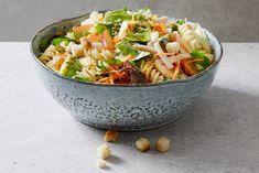 Goedgevulde salade met pasta, appel, peen, eikenblad sla, ijsbergsla, gerookte kip, honing-mosterddressing en croutons.