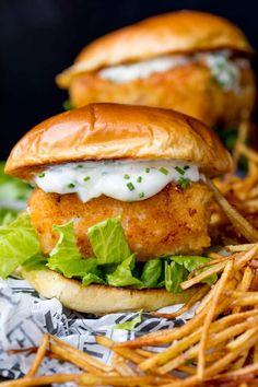 Close up image of breaded haddock burger on brioche bun with lettuce and chive-speckled mayonnaise. Shoestring fries to the right of the burger. A second burger in background.