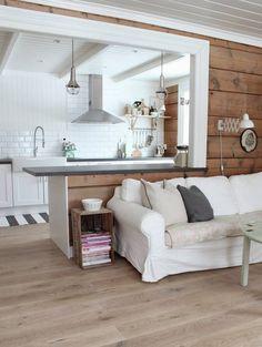 Surowe deski na ścianie salonu nadały mu rustykalny charakter. Na tle ciemnego drewna ładnie prezentują się białe kanapa, lampa na wysięgniku i szeroka listwa wokół prześwitu łączącego pokój dzienny z kuchnią. W charakterze stolika pomocniczego z półką na czasopisma użyto starej drewnianej skrzynki.