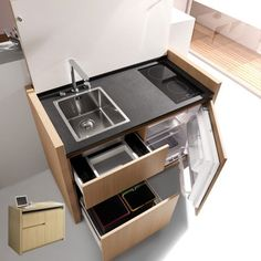 Cuisine compacte Kitchoo composée d'un évier, d'un robinet télescopique  d'une table à induction, d'un réfrigérateur-congélateur, d'un lave-vaisselle, de prise de courant…