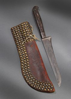 "Crow Knife Case and Knife.  c.1870. Knife case on heavy saddle skirting over 130 square shank tacks.  Knife in scabbard 15"" overall length.  Sherwoods Spirit of America."