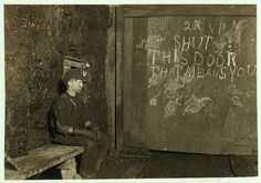 Vance, a Trapper Boy, 15 years old. Has trapped for several years in a West Va. Coal mine. $.75 a day for 10 hours work. All he does is to open and shut this door: most of the time he sits here idle, waiting for the cars to come. On account of the intense darkness in the mine, the hieroglyphics on the door were not visible until plate was developed. 1908