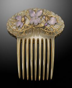 René Lalique   Art Nouveau hair comb applied with three foil backed frosted glass violets. Mounted in gold.
