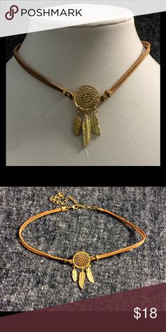 "Gold Toned & Leather Dreamcatcher Choker Chic and trendy, this Choker is the perfect accent for any outfit. A gold Toned Dreamcatcher about 1"" in diameter adorned by feathers that fall about an inch, this intricate charm is stranded on a sturdy doubled rope with grommets on either side. Necklace is 13"" long and has a 5"" extender. Make a Wish Jewelry Necklaces"