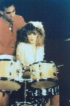 some guy watching Stevie as she tries her hand at playing the drums  ~ ☆♥❤♥☆ ~   dressed in all her onstage finery