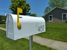 white mailbox with yellow flag and modern house numbers. DO THIS NOW.
