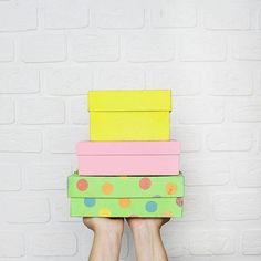 Foto segurando caixas coloridas em frente a uma parede de tijolinhos branca em um quarto iluminado e clean