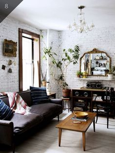 Modern boho living room design in a loft featuring white painted brick walls, a mid-century modern coffee table, an antique gold framed mirror, crystal chandelier, vintage finds, and plants - Eclectic Decorating Ideas & Decor