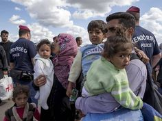 A family walk past Hungarian police to board a bus in the village of Roszke (Reuters) Syrian Children, Syrian Refugees, David Cameron, About Uk, Police, Age, How To Plan, Board, Law Enforcement