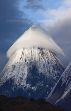 Klyuchevskaya Sopka Mountains in Russia, Lenticular Cloud over the Mountain,it is a stratovolcano, the highest active volcano of Eurasia. Its steep, symmetrical cone towers about 100 kilometres from the Bering Sea. and is part of the natural Volcanoes of Kamchatka