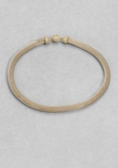 A simple and sophisticated necklace made from a tightly woven metal cord.