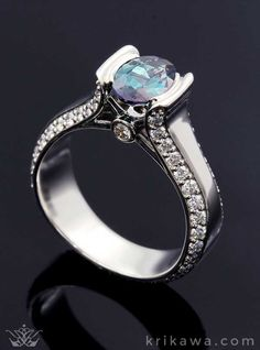 Stop the show with this Modern Juicy Liqueur Engagement Ring! Sparkling diamonds follow the luscious curves up to your choice of center stone! Pictured in platinum with an oval color-change alexandrite and diamond accents.Start the fun and easy design process by selecting your favorite metal and stones....