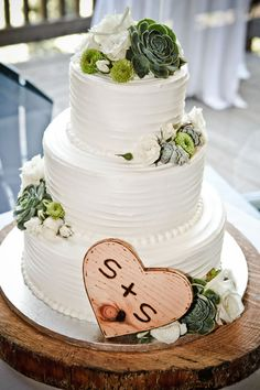 "A sweet white wedding cake topped with succulents. We just adore the couple's initials ""carved"" into the wooden heart. Freedom Bakery and Confections."