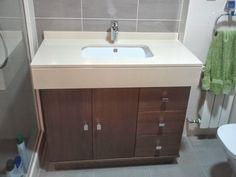Trabajo realizado en Valdemoro. Madrid Fabricación e instalación de mueble en madera color wengue barnizado y encimera con faldón en compac marfil stone para lavabo bajo encimera..