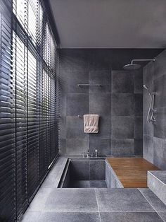 Sunken bath tub, natural stone flooring, dark grey tiles - this bathroom is somewhere we'd love to have a long soak in!