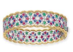 A MULTI-GEM AND DIAMOND BRACELET, BY BUCCELLATI Desgined as an openwork 18k white gold hinged bangle, set with a series of circular-cut diamond, ruby and sapphire foliate motifs, spaced by circular-cut emeralds, to the textured 18k gold trim, 2¼ ins. diameter Signed M. Buccellati for Mario Buccellati, Italy