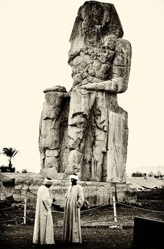 1900s vintage photo of one of the Colossi of Memnon (known to locals as el-Colossat, or es-Salamat) massive stone statues of Pharaoh Amenhotep III. For 3,400 years they have sat in the Theban necropolis, across the River Nile from the city of Luxor. Egypt