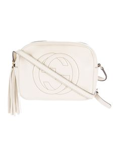 Creme pebbled leather Gucci Soho Disco crossbody bag with gold-tone hardware, adjustable flat shoulder strap, embroidered logo accent at front, tonal canvas interior lining, dual slit pockets at interior walls and zip closure at top featuring tassel embellishment. Includes dust bag. Shop Gucci designer bags online at The RealReal.