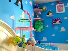 Pixar Themed Nursery, For our first baby, we wanted to touch on everything Pixar. While the room screams Toy Story, we actually referenced all of the movies and some Pixar shorts., Our homemade baby mobile, a 100% reference to Toy Story. The rings that make up the mobile are a reference to the outfit Bonnie wore in Toy Story 3. All of the toys are hanging from claws, a reference made in all 3 Toy Story movies.  , Nurseries Design