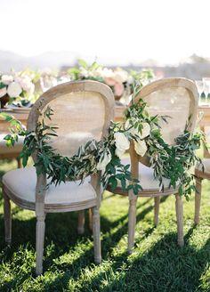 Elegant + organic garland draped sweetheart chairs: http://www.stylemepretty.com/2016/01/04/intimate-sunstone-vineyards-wedding/ | Photography: Jose Villa - http://josevilla.com/