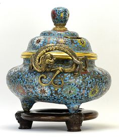 A Chinese Cloisonne Censer, likely Qing Dynasty, the censer mounted with handles in the form of a sinuous dragon with back turned head and bifurcated tail, the body of the censer enameled with lotus bearing meander on a turquoise ground, with shaped cloisonne top and custom hardwood base, the base of the censer restored, appx. 12 in. W, 12 1/2 in. H. on base.