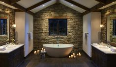 stone walls behind bathroom vanities and sinks, dark wood cabinets, marble countertop, sconces, dark wood ceiling beams. freestanding white bath tub