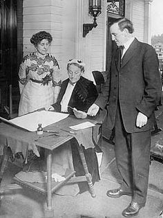 Abigail Scott Duniway signs Oregon's Equal Suffrage Proclamation on Nov. 30, 1912 as Governor Oswald West and Viola M. Coe watch.