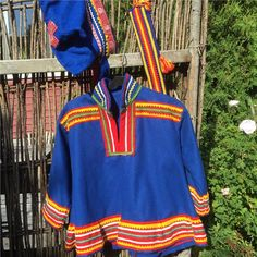 Here is a Sami costume for children. Frock with belt and hat. Blue cap. Finnish design by Noitarumpu Rovaniemi, Finland. The suit is in very condition. However, missing loop on pewter buckle. Chest width 96 cm. Length back collar 56 cm apart. Sleeve length 36 cm. 5/5