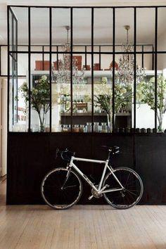 Bicyclette blanche sur fond de verrière noire. La cuisine est en fête. On y remarque deux très beaux lustres. Conso par Silenceondecore.
