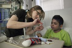 Melissa Ramirez, a child life specialist at Wesley Medical Center, helps Julio Garcia, 9, insert an IV into a doll. She helps children feel more comfortable in the hospital, including before they go into surgery. (March 14, 2013.)   Mike Hutmacher/The Wichita Eagle