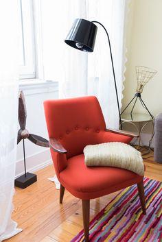 Roter Sessel, schicke schwarze Stehlampe und ein toller bunter Teppich.