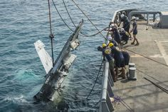 These photographs and video show the wreckage of a Boeing F/A-18F Super Hornet being salvaged after the warplane plummeted into the Arabian Sea in 2015.