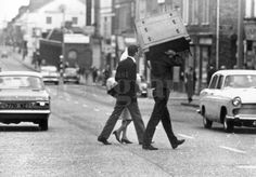 Riots : Belfast. August 1969. House-holder moves his furniture across the Crumlin Road in the Hooker Street area, as Protestants and Roman Catholics exchange homes. (4/8/69)