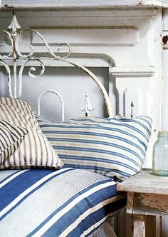 I love ticking!! And notice the headboard treatment .  . . an old iron gate layered over an old mantle!  Adore!! ♥