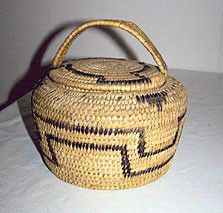 This is a native American covered coiled basket probably made by the Pima or Papago Indians. It measures 6 inches wide by 6 inches high and has a black geometric woven in pattern. This basket is in ve