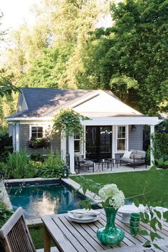 Small back yard. Swimming pool. Arbor. Grey. Black. White. French Doors.