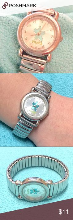 Mudd silver metal band w/ aqua flower face watch. Mudd silver metal band w/ aqua flower face watch. Stainless steel back.  Elasticized wrist band.  7.5 inches around NOT on or stretched out. Stretches wide to 12 inches so lots of room. Fits my six inch wrist comfortably with no stretching when on.  Band a tiny bit worn.  Needs new battery. Priced lower to sell. Mudd Accessories Watches