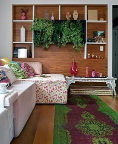 A designer de interiores Amanda Borges investiu em tons de rosa na sala onde predomina a madeira do piso e da estante. O verde das plantas e outros detalhes equilibram o ambiente