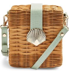 Sweeten your summery vibe in this mini wicker tote designed in a rectangular shape with a beachy shell clasp.