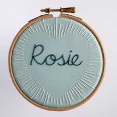 Hand-embroidered name surrounded by a sunburst heart, by Squibblybups.